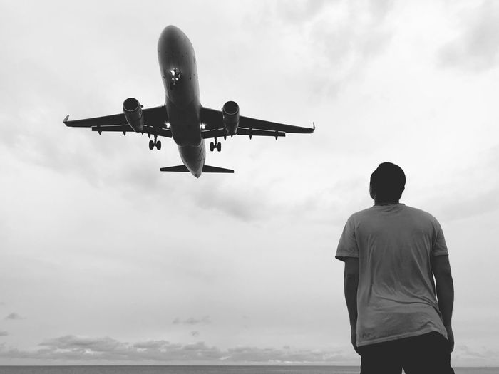 Man looks at the plane that flies over them. 2018 Airplane Wing Dreems Airplane Air Vehicle Sky Cloud - Sky Rear View Mode Of Transportation Flying Transportation Travel Real People Low Angle View Lifestyles Airport People Day Mid-air Men Motion Outdoors Nature Moments Of Happiness It's About The Journey