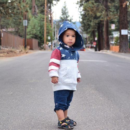 Boy in hood standing on road
