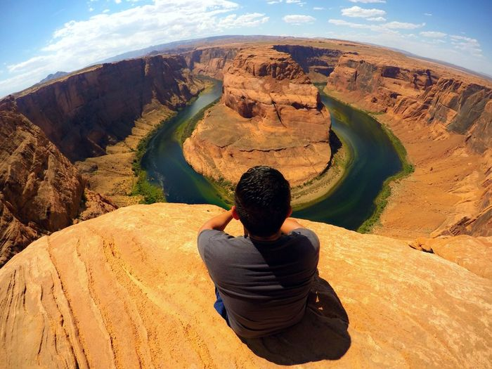 High Angle View Of Man Sitting On Mountain At Horseshoe Bend