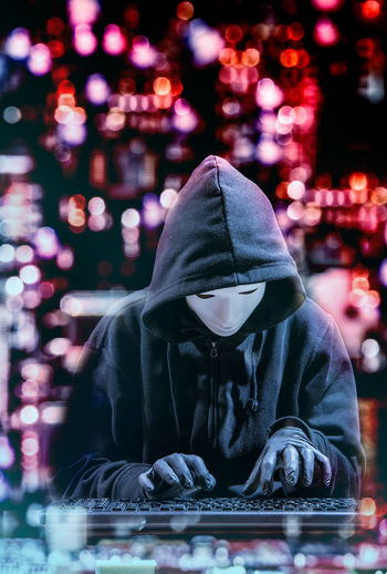 Computer Hacker Wearing Mask And Hooded Shirt While Tying On Keyboard Against Illuminated Lights