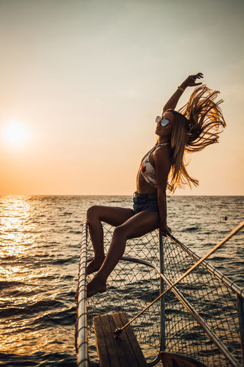 Water Sea Sunset Sky Leisure Activity Young Adult One Person Beauty In Nature Young Women Real People Lifestyles Nature Scenics - Nature Women Full Length Hairstyle Fashion Sun Horizon Over Water Outdoors Human Arm Arms Raised Beautiful Woman