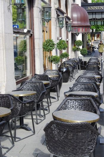 Chairs and tables at sidewalk cafe amidst buildings