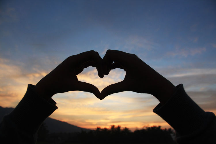 Cropped hand of person making heart shape against sky