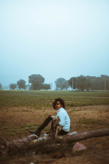 Full length of woman sitting on field against clear sky