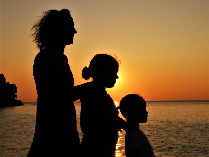 Side view of silhouette mother with daughters standing at beach against sky during sunset