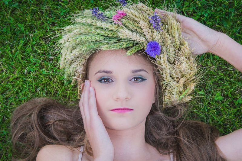 Close-Up Portrait Of Beautiful Young Woman Lying Down On Grass Wearing Flowers With Hand On Face