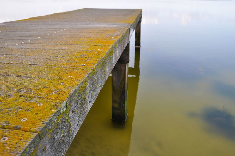 Close-up of yellow pier on lake