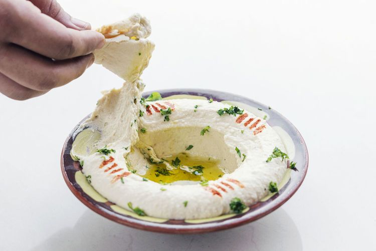 lebanese hummus dip DIP Mezze Snack Tapas Bowl Chickpea Chickpea Dip Close-up Day Food Food And Drink Freshness Healthy Eating Healthy Lifestyle Holding Human Body Part Human Hand Hummus Indoors  Lebanese Middle Eastern Food Ready-to-eat Traditional White Background