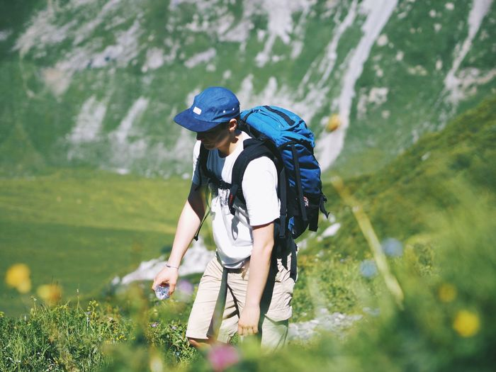 Hiker with backpack on field against mountain