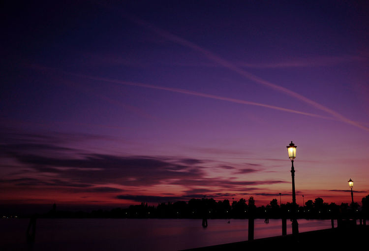 Lake in silhouette city against sky at dusk