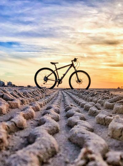 Bicycles on bicycle against sky during sunset