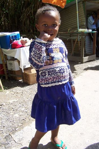 Black Girl Blue Child Childhood Cute Girls Happiness Looking At Camera Outdoors Poor Girl Real People Smiling Standing Streetlife Sunlight