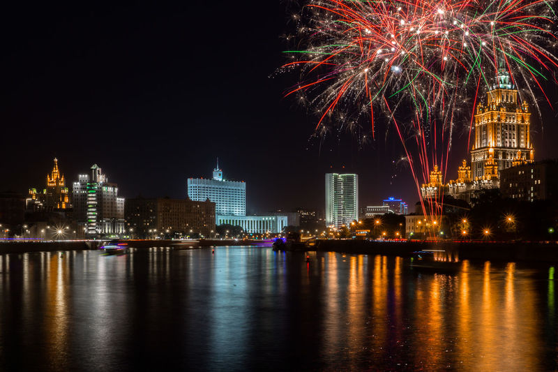Firework display over river by buildings in city at night