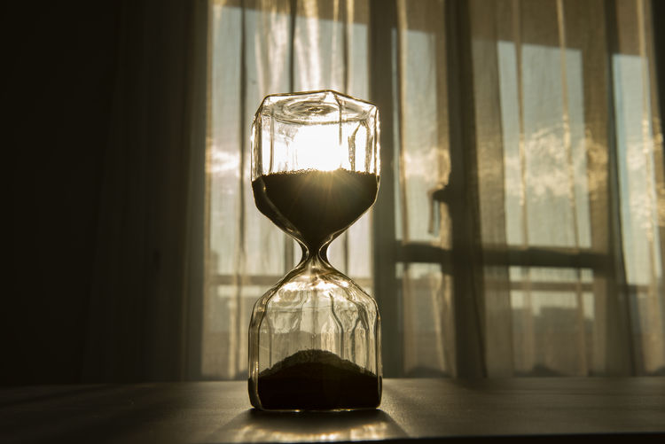 Close-Up Of Hourglass On Table By Window