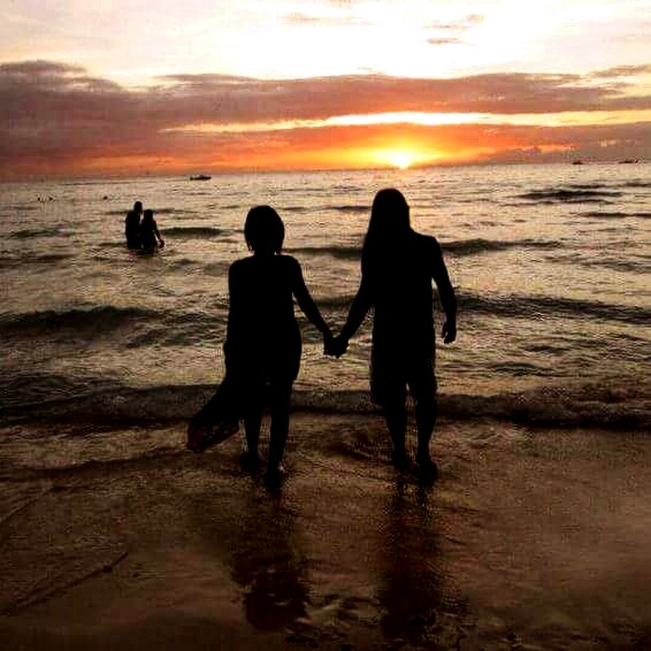 sea, sunset, beach, silhouette, two people, water, togetherness, leisure activity, real people, nature, lifestyles, love, vacations, sand, sky, full length, childhood, horizon over water, scenics, boys, beauty in nature, men, bonding, outdoors, day, adult, people