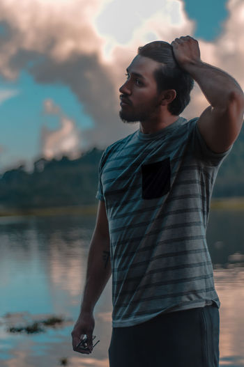 Young man looking away while standing on lake against sky