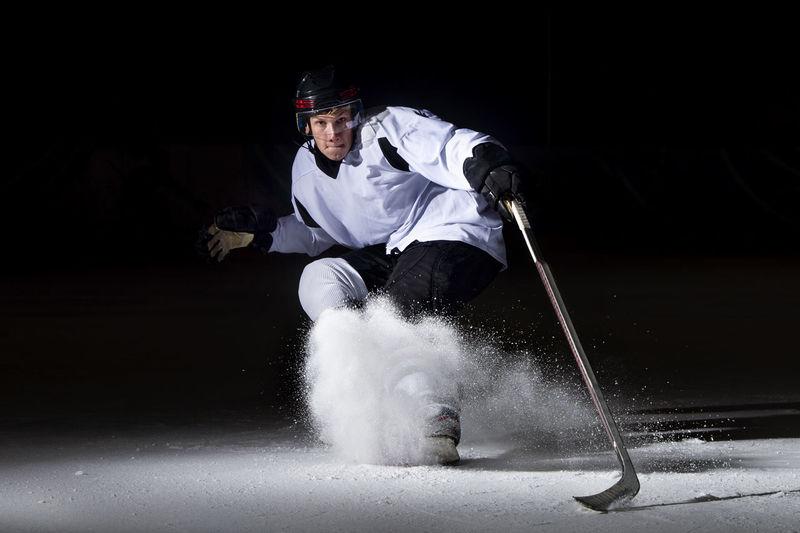 Portrait of man playing ice hokey at night