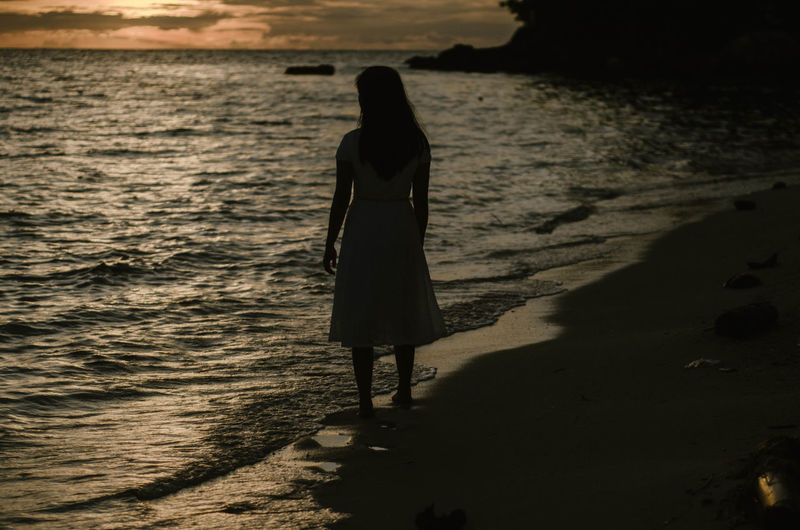 Rear view of silhouette woman standing at beach