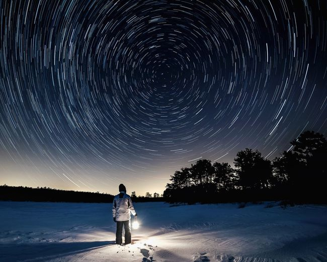 Man standing on snow field against sky at night