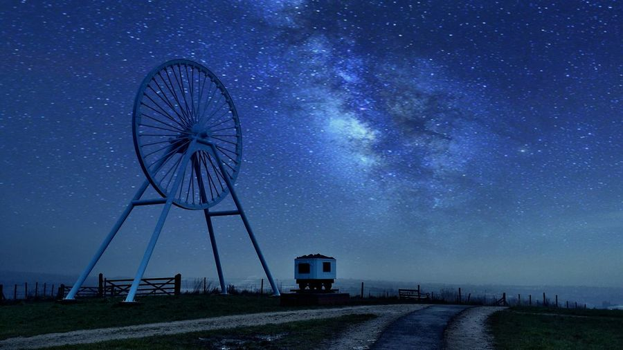 Apedale colliery wheel on field against starry sky
