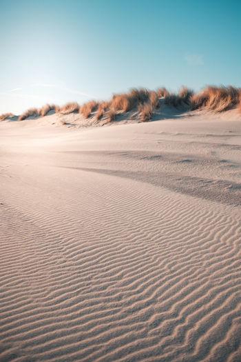 Sand dunes at desert against clear sky