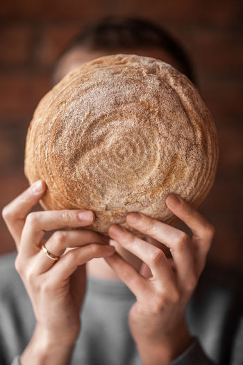 The guy holds round bread in front of his face. Unrecognizable person. Food Food And Drink Lifestyles Real People Lifestyle Hand Human Hand One Person Human Body Part Indoors  Holding Adult Close-up Bread Freshness Focus On Foreground Portrait Bakery Selective Focus Women Front View Headshot Unrecognizable Person Hands Fingers