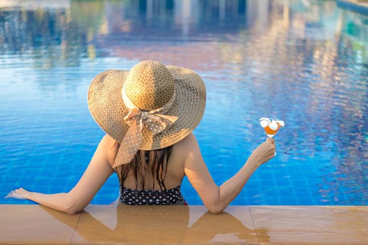 Woman sitting on swimming pool