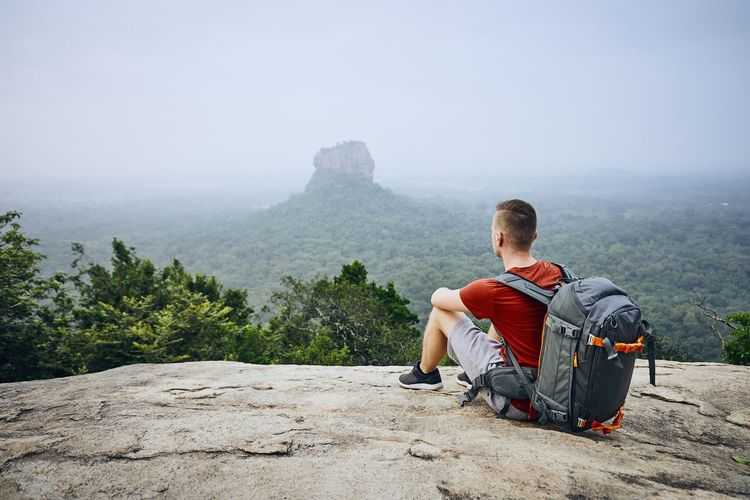 Young man with backpack against Sigiriya Rock (UNESCO World Heritage Site). View from Pidurangala Rock in Sri Lanka. Man Travel Travel Destinations Backpack Backpacking Backpacker Hiking Sigiriya Sri Lanka Tourist People One Person Wanderlust Exploring Adventure Independence Freedom Vacations Scenics - Nature Nature Landscape UNESCO World Heritage Site Lifestyles Rock - Object Young Adult