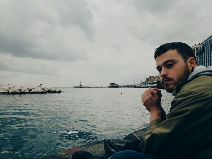 Young man sitting on rock against sea
