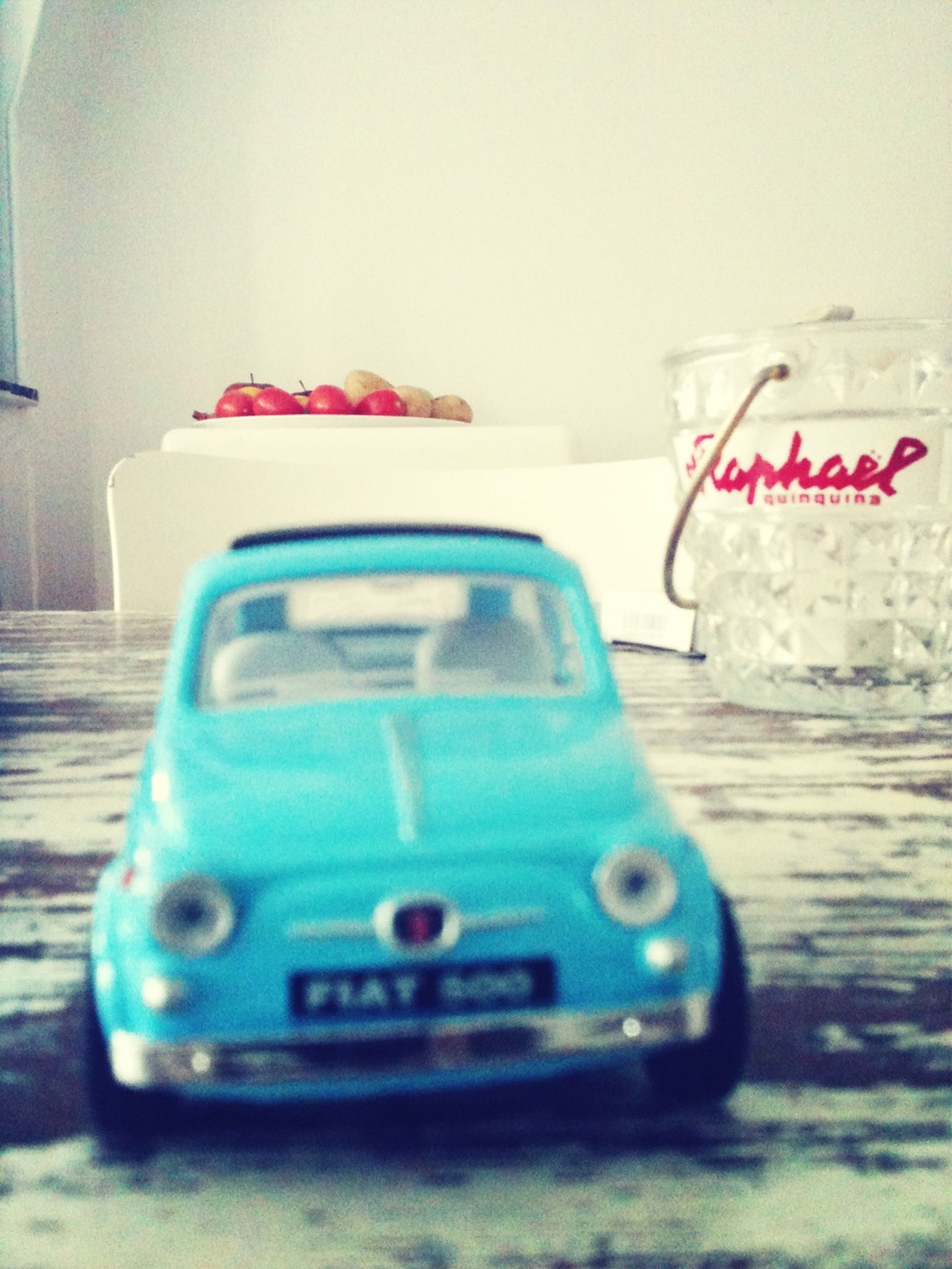 indoors, close-up, still life, table, selective focus, focus on foreground, communication, car, single object, no people, text, technology, toy, day, plastic, western script, open, land vehicle, transportation, pen