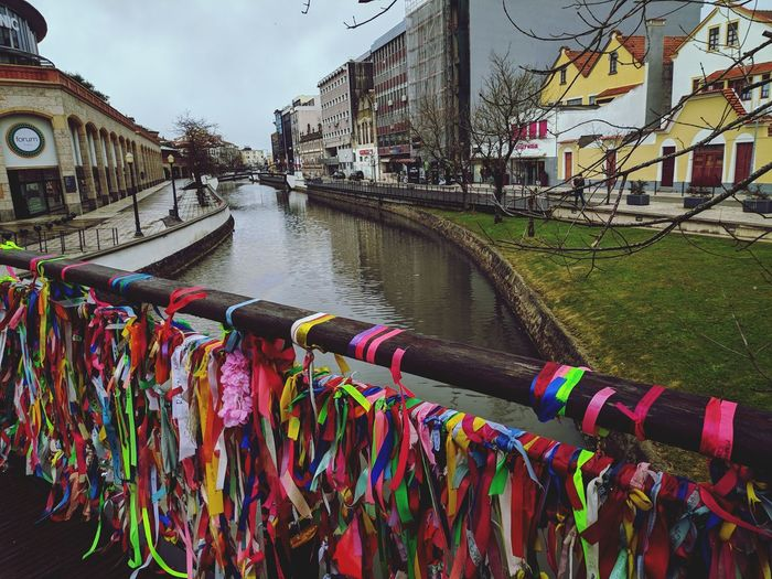 Multi colored ribbons on railing over canal by buildings