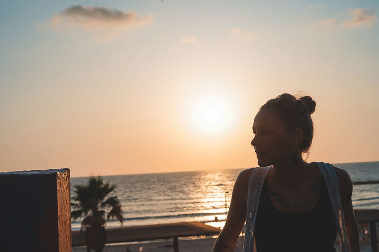 Woman Beauty In Nature Contemplation Female Hairstyle Horizon Horizon Over Water Leisure Activity Lifestyles Nature One Person Orange Color Outdoors Real People Scenics - Nature Sea Sky Standing Sun Sunlight Sunset Water Women Young Adult