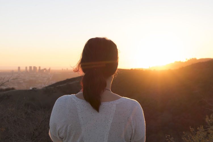 Rear View Of Woman Looking At Mountains Against Sky During Sunset
