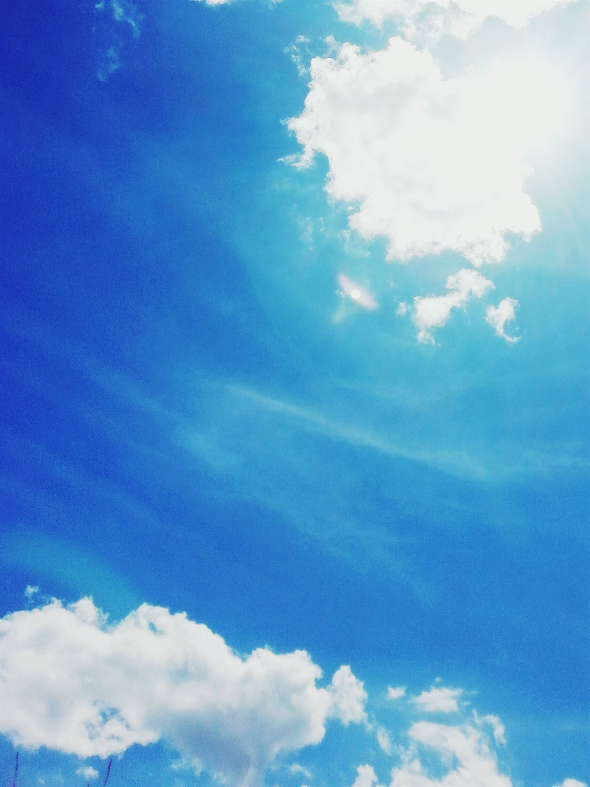 low angle view, blue, sky, cloud - sky, beauty in nature, tranquility, sky only, scenics, nature, cloud, tranquil scene, cloudy, sunlight, cloudscape, idyllic, day, backgrounds, outdoors, no people, sunbeam