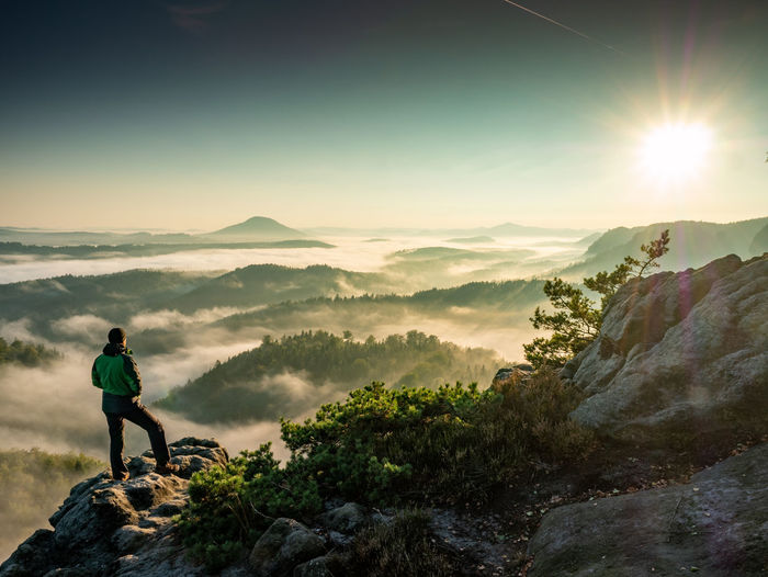 Single man hiker on a mountain trail. mountain look into misty valley