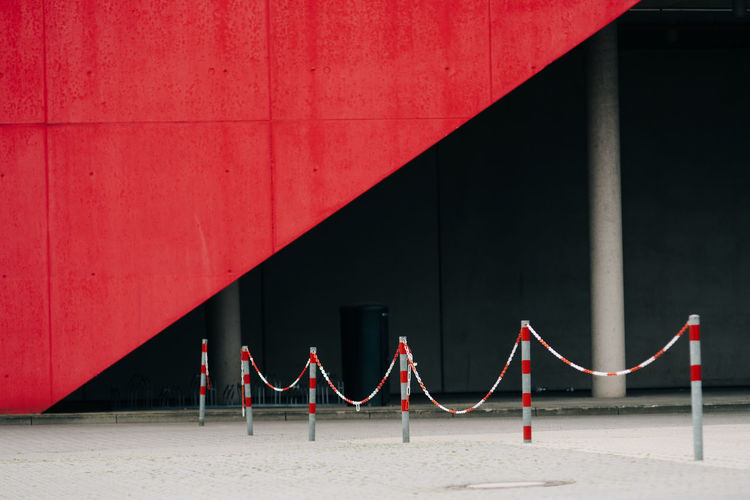 Metallic railing against red wall in city