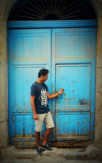 Full length of young man standing against blue door