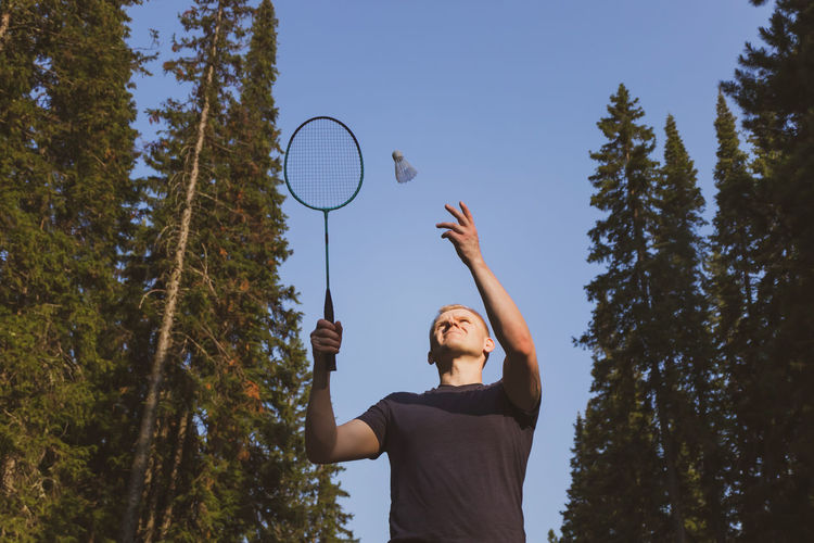Low angle view of man playing badminton against sky