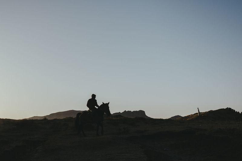 Men riding horse on land against sky