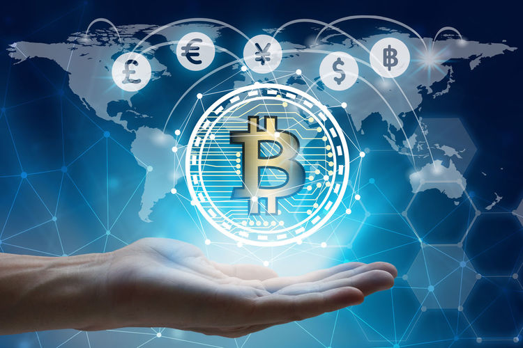Digital Composite Of Cropped Hand With Bitcoin Against World Map