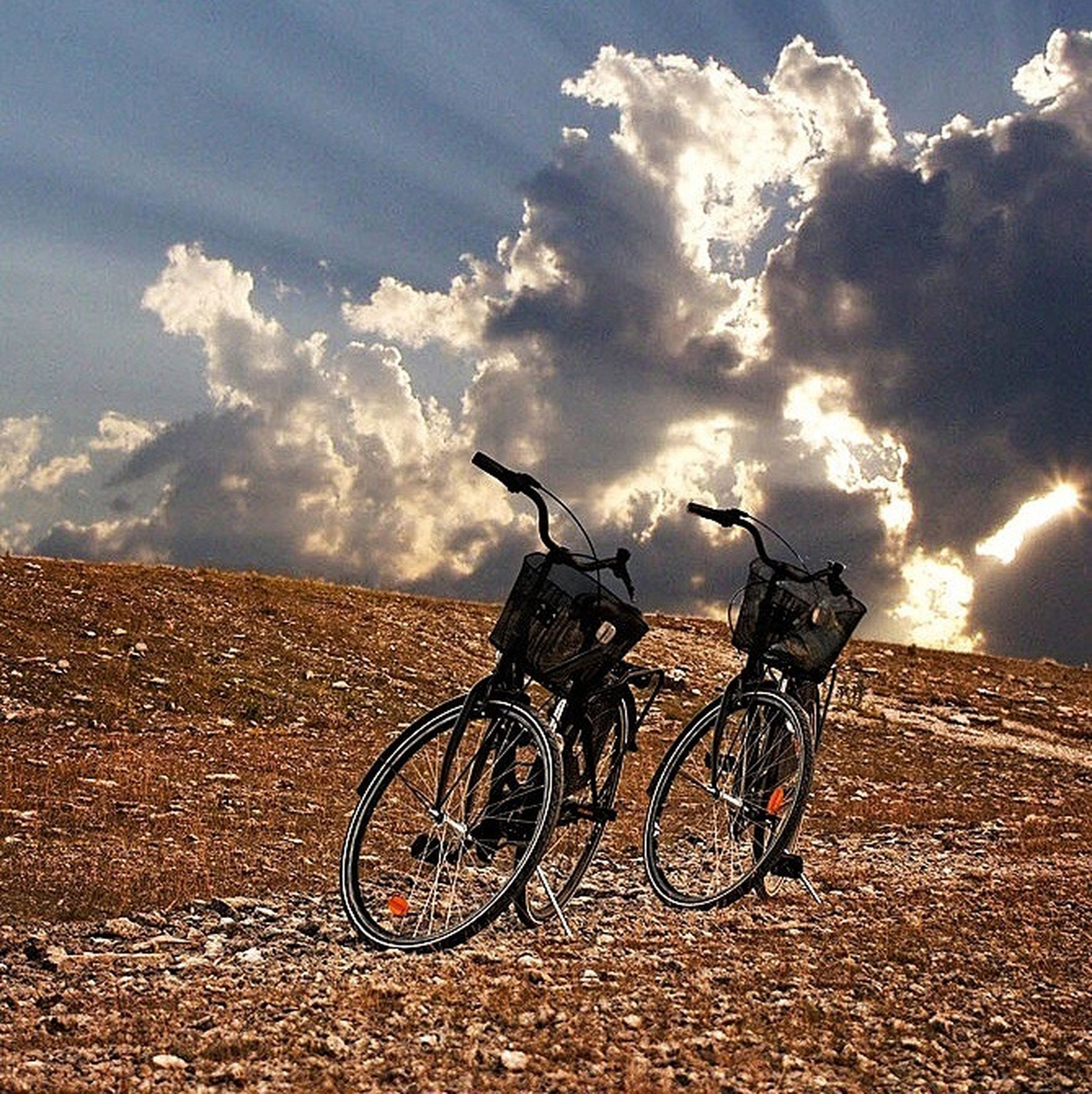 bicycle, transportation, sky, land vehicle, mode of transport, stationary, parked, cloud - sky, parking, landscape, wheel, tranquility, day, outdoors, cloud, nature, cloudy, tranquil scene, no people, field