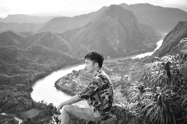 Side view of young man looking at mountains