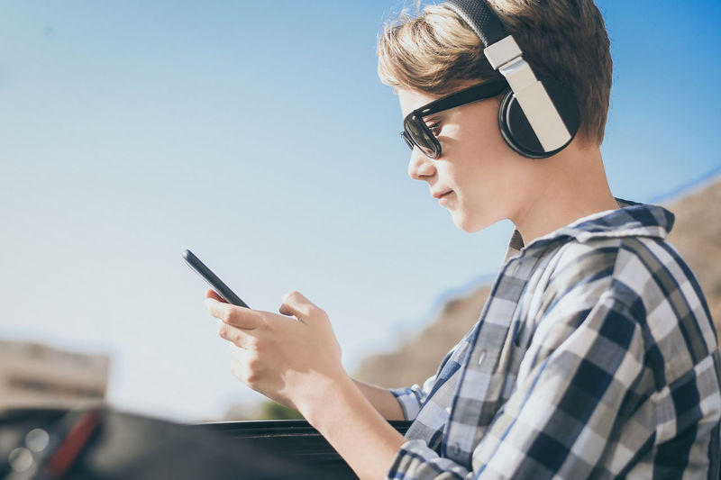 Side view of boy using smart phone against sky