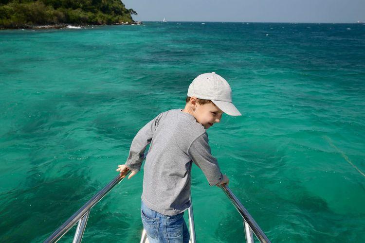Boy standing in sea against sky