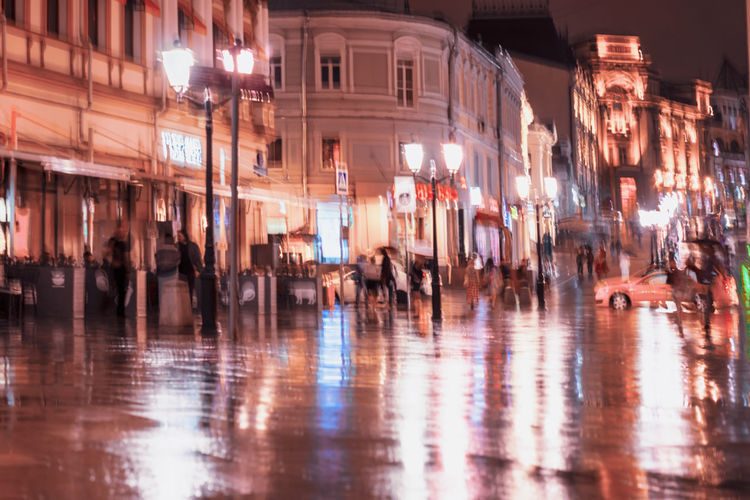 City street in rainy late evening, abstract background of blurred people figures under umbrellas, orange brown tones. Intentional motion blur. Vivid illumination from lanterns and shop windows Illuminated City Night Motion City Rainy Rain Blurred Motion Blur Abstract Evening Street Bright People Reflection Lamps Pavement Umbrella City Life Outdoors Light Group Of People Architecture Crowd