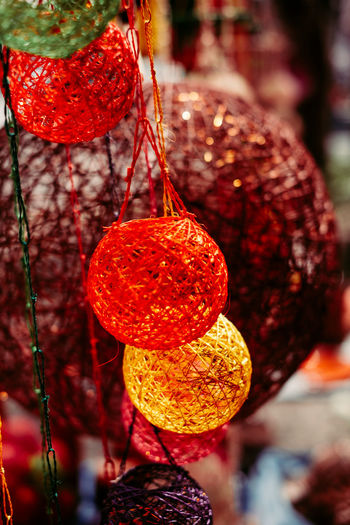 light lanterns made from Abaca plant. hand woven into ball shapes Hanging Close-up No People Red Day Tree Decoration Outdoors Selective Focus Orange Color Sunlight Christmas Holiday Light Lantern Abaca Woven Pattern Backgrounds Colorful Object Portrait Handcraft Design Thread Autumn Mood Holiday Moments Analogue Sound Streetwise Photography The Art Of Street Photography