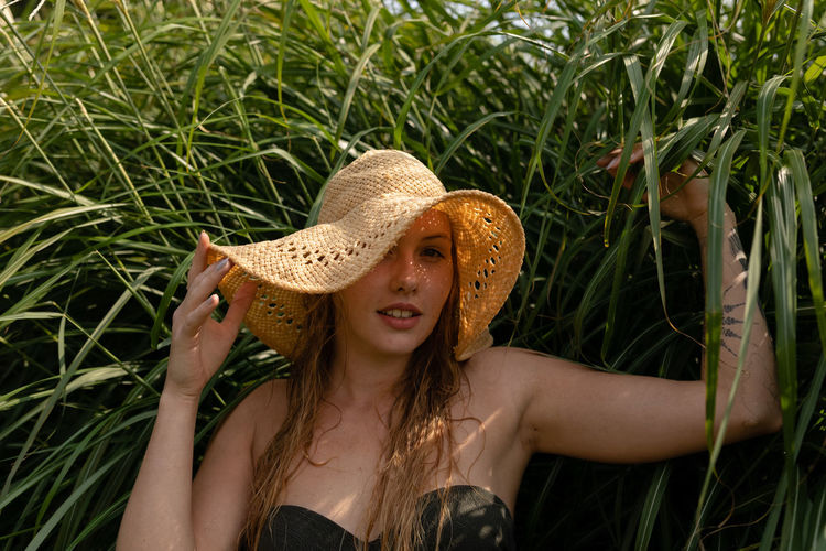 Portrait of young woman wearing hat while standing against plants