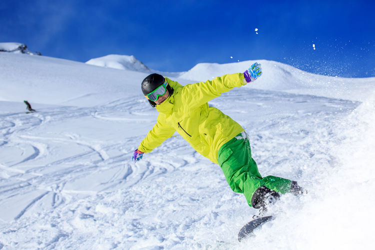 Low Angle View Of Young Man Skiing On Snowcapped Mountains During Winter