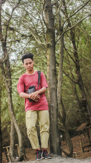 Young man standing against trees in forest