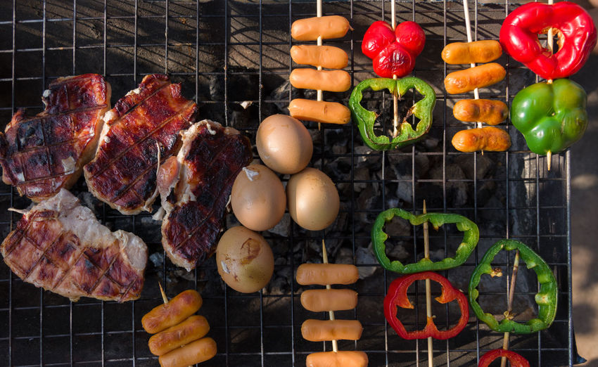 Directly above shot of meat with vegetables and eggs on barbecue grill